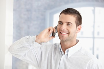 Young man talking on mobile phone smiling