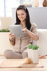 Pretty girl using tablet at home smiling