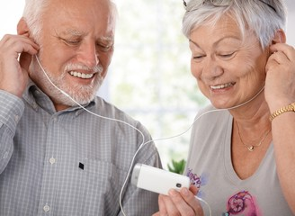 Happy elderly couple with mp3 player