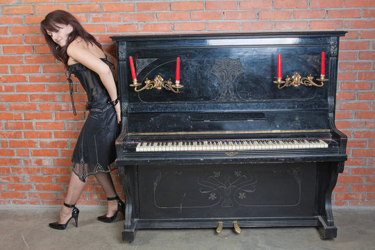 woman in black dress shifts the heavy-weight piano