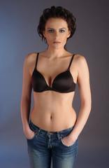 Studio photo of slim, sexy brunette model wearing jeans and bra.