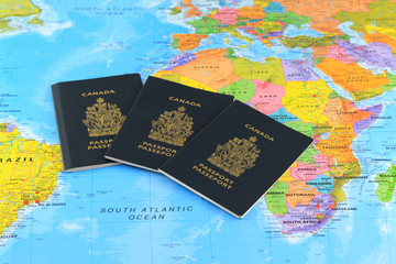 Three Canadian passports ath the world map