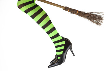 Stripey legged witch flying on her broomstick.
