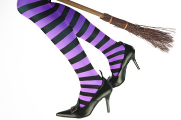 Stripey legged witch flying on a broomstick.