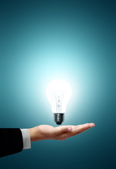 Light bulb in hand on green background