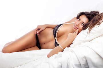 portrait of beautiful smiling young woman lying in bed in her un