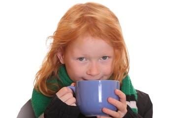 Rothaariges Mädchen trinkt aus einem Becher Tee