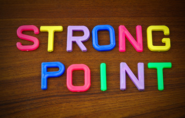 Strong point in colorful toy letters on wood background