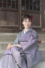 神社の階段に座る女性