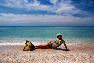 Blonde girl in yellow flippers and swimming mask on the sandy se