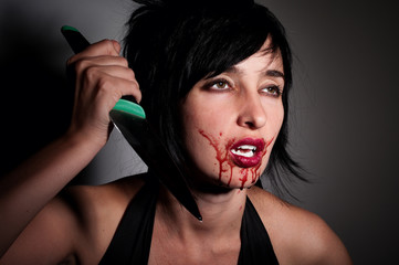 Crazy vampire woman with blood on her face