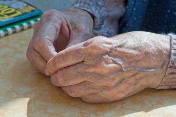 Alte Hände auf dem Tisch