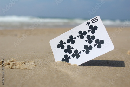 Playing Card The 10 Club In Sand Beach Background