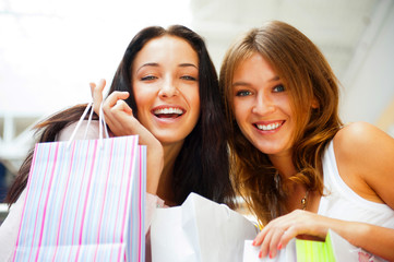Two happy women at a shopping center with bags. Seasonal prepart