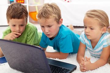 Focused kids looking at laptop computer