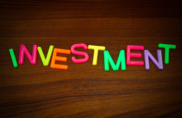 Investment in colorful toy letters on wood background