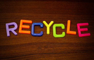 Recycle in colorful toy letters on wood background