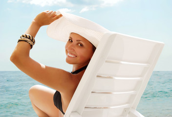 Happy smiling young woman in white hat at the sea view