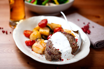 Beef steak with herb sauce and roasted vegetables