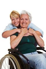 Frau umarmt Seniorin im Rollstuhl