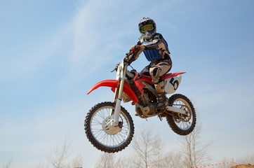Motocross motorbike racer performs a jump efficient