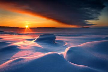 Photo sur Plexiglas Bleu nuit Snowy seascape with dark cloud and rising sun