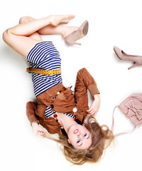 Attractive young lady lying in studio in casual fashion clothes