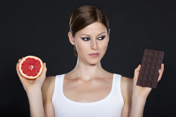 Young beautiful woman holding chocolate and grapefruit in her ha