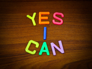 Yes I can in colorful toy letters on wood background