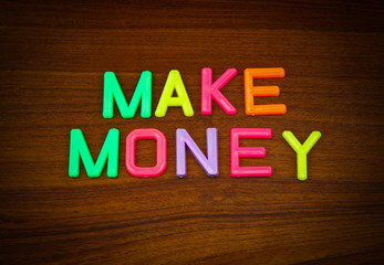 Make money in colorful toy letters on wood background