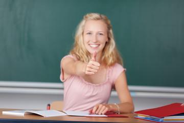 junge frau in der schule zeigt daumen hoch