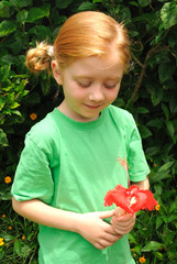 Young girl looking at red flower in a garden