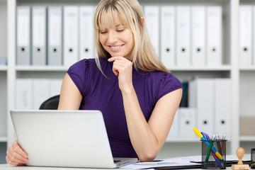 junge frau im büro schaut auf ihr notebook