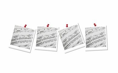 Spartiti musicali appesi con puntine da disegno su fondo bianco
