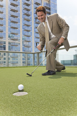 Successful Businessman Playing Golf on Skyscraper Rooftop