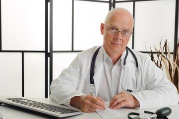 Arzt sitzt lächelnd am Schreibtisch