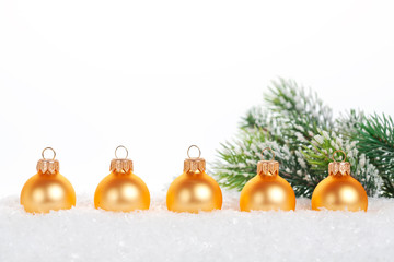Gold balls in snow on white