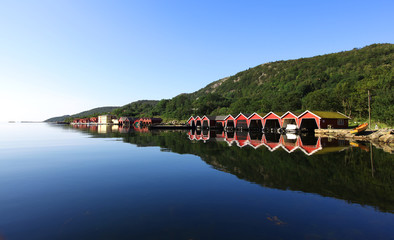 Garden Poster Scandinavia Row of red colored boathouses in fjord in Scandinavia