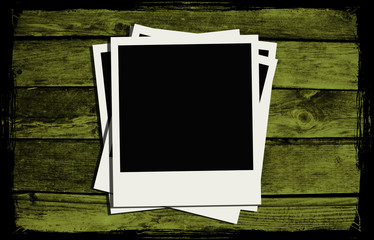 Polaroid frames over abstract wooden background