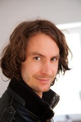 junger mann close up braune haare vor fenster