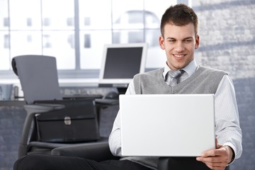 Young businessman browsing internet smiling