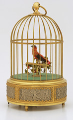 Bird in a vintage gold musical cage