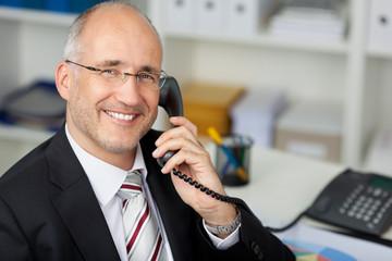 freundlicher geschäftsmann am telefon