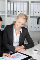 blonde frau im büro mit ihrer kollegin