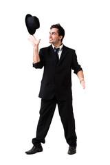 junger Mann balanciert seinen Hut auf Zeigefinger