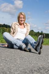 Inline skates young woman sitting asphalt road