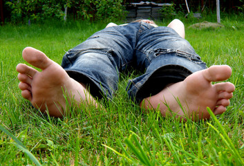foot and a heel of the young man laying on a grass