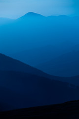 blue color of mountains during sunset