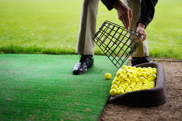 Wall Mural - Yellow golf balls pouring out of basket