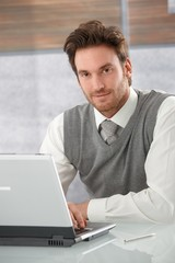 Portrait of handsome man with laptop smiling